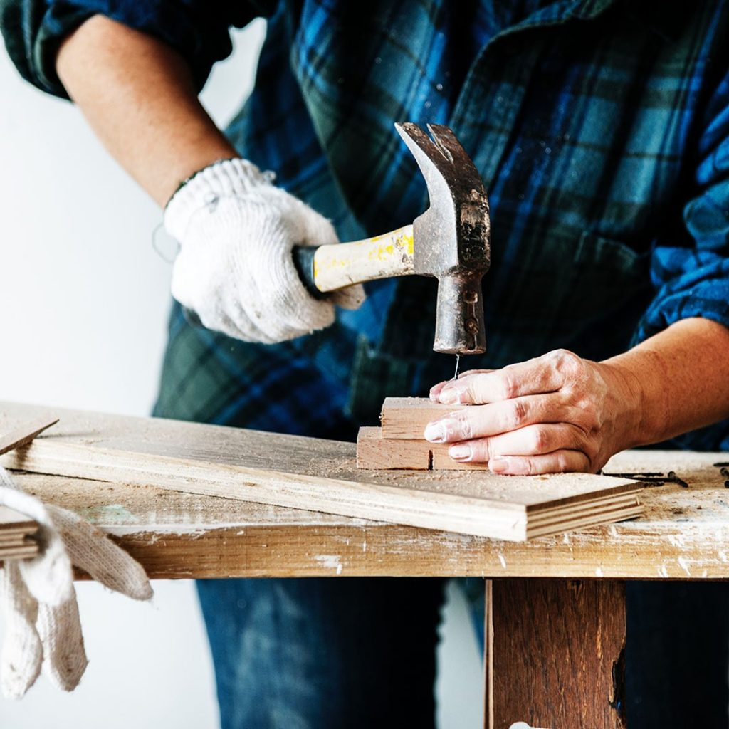 Carpenter doing manual work with hammer and nail