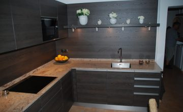 Dark style wooden kitchen with marble countertop